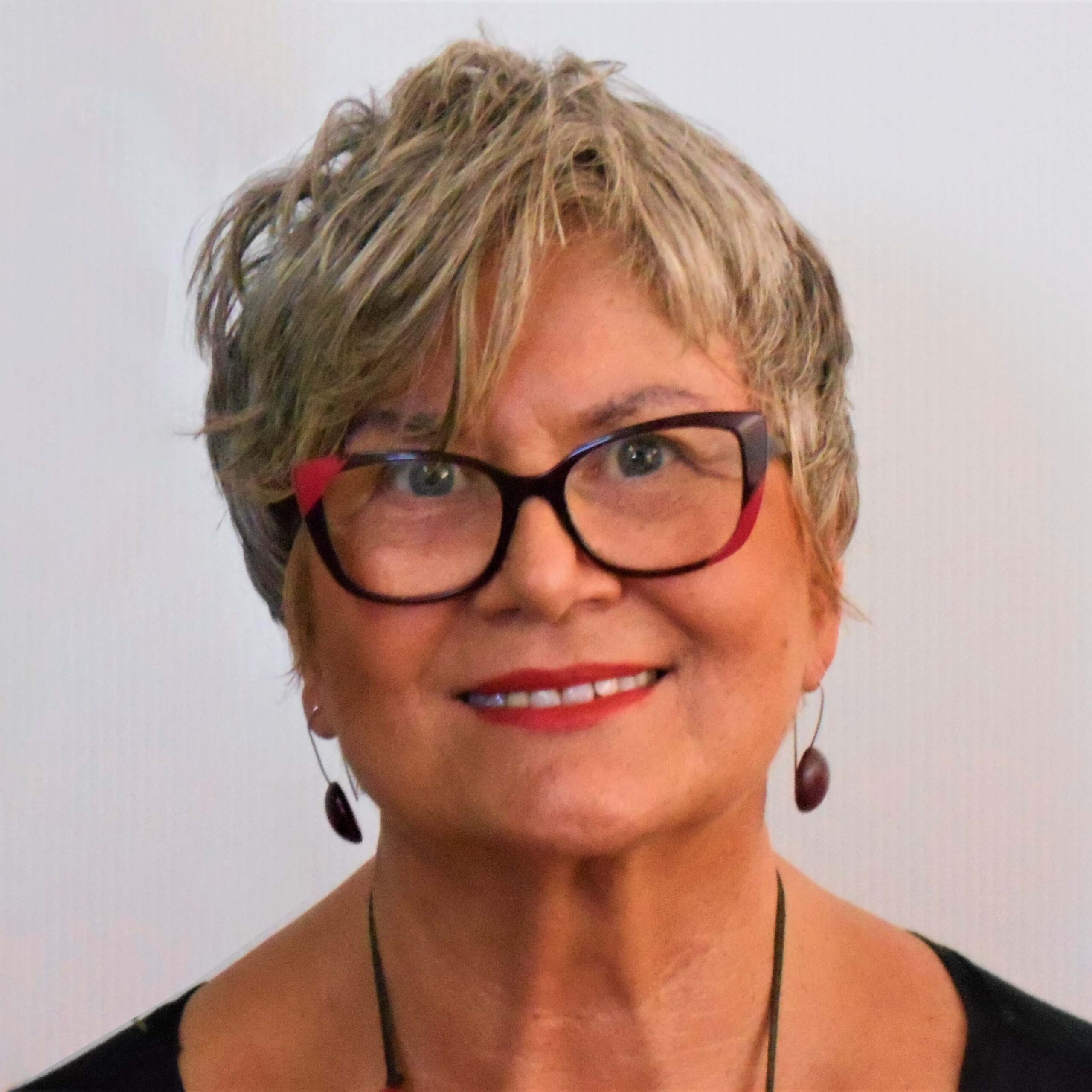 Profile photo of a Elizabeth Szczepanska, lights skin female, 60's, red and black frame glasses and earrings